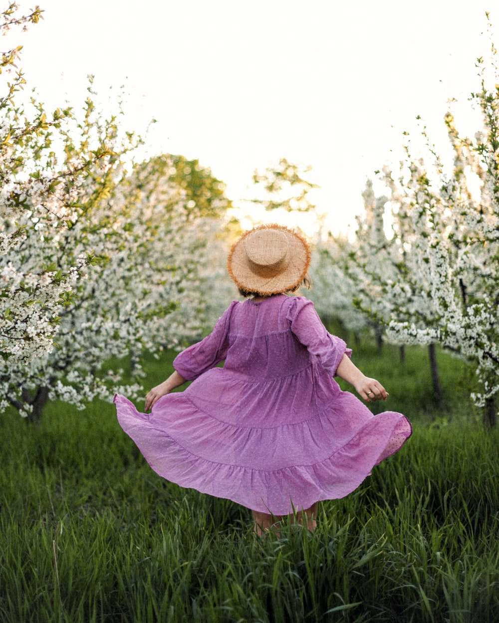 woman in pink dress and brown sun hat sitting on green grass field during daytime