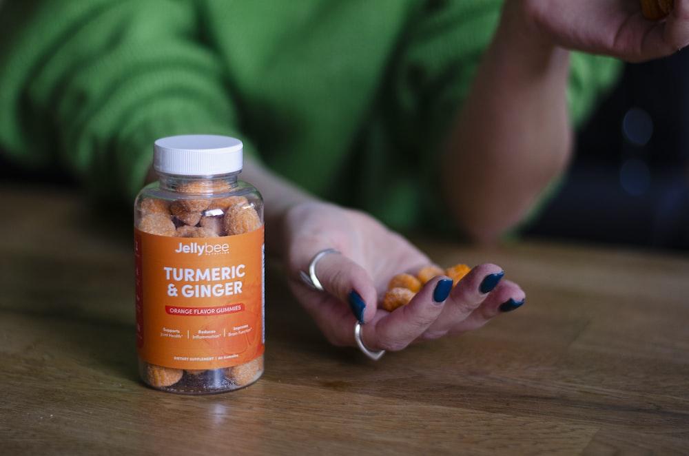 person holding orange labeled bottle