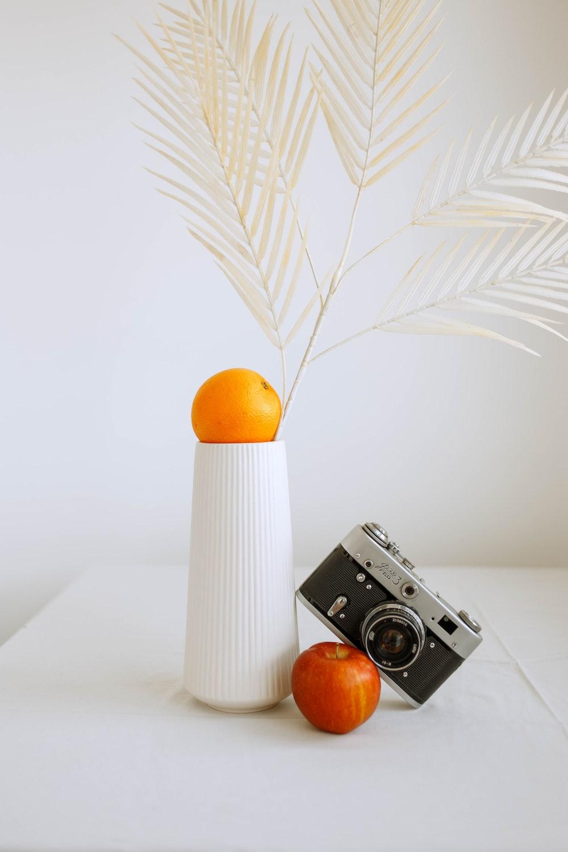 white and black camera beside orange fruit