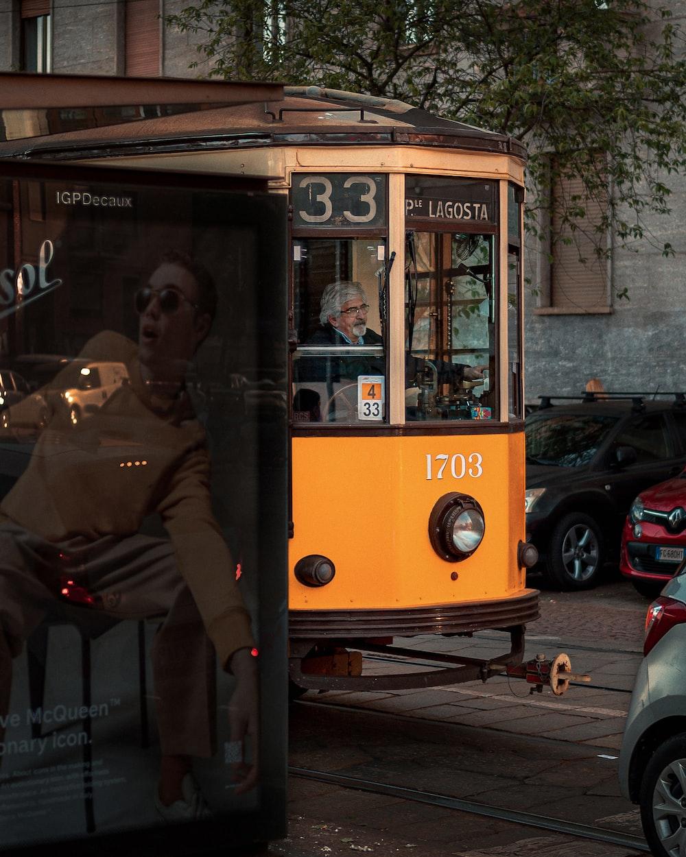 man in brown jacket sitting on yellow bus during daytime