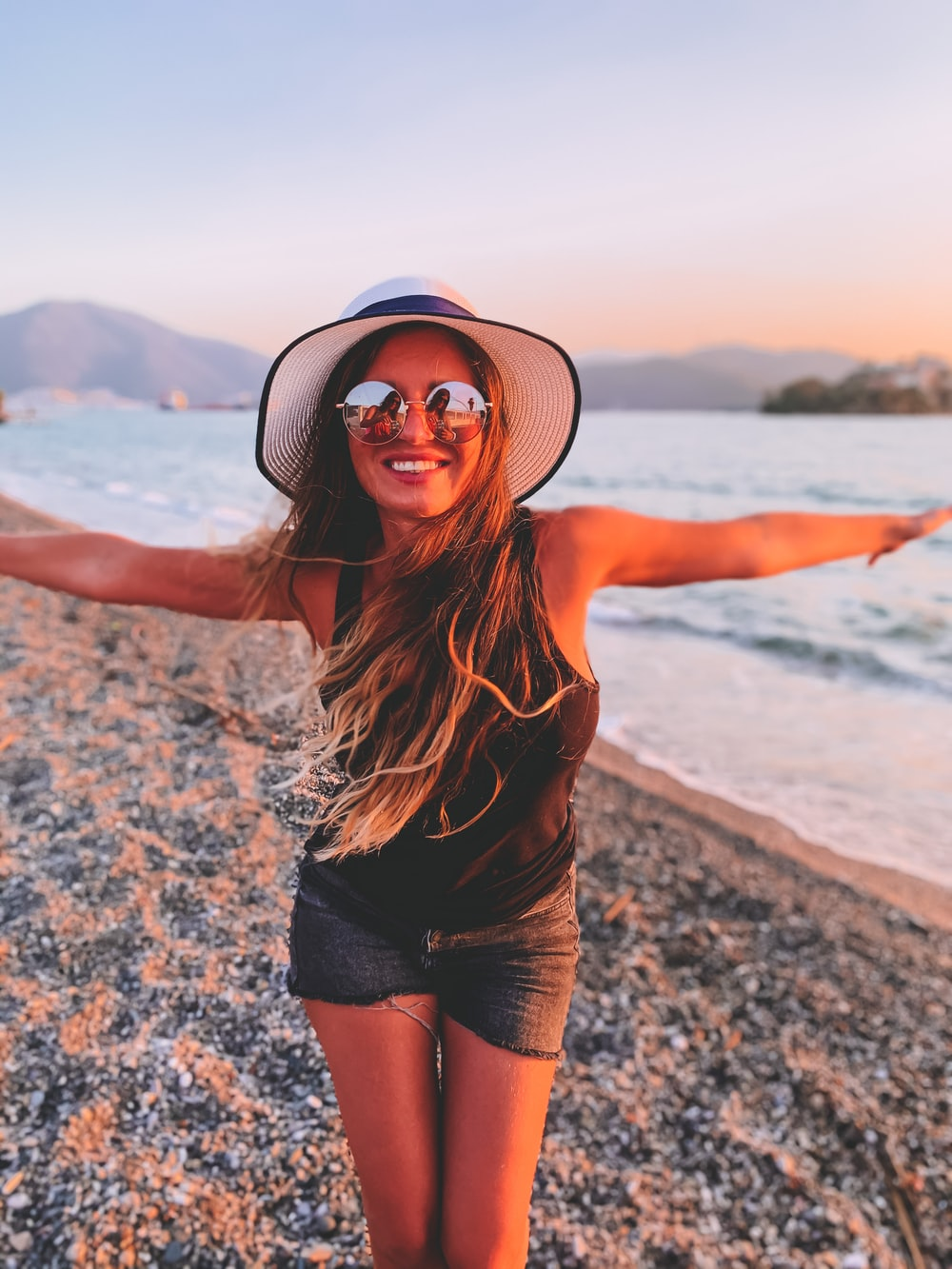 woman in black tank top and black shorts wearing black sun hat standing on beach shore