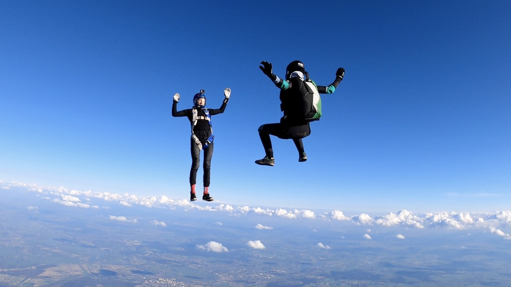 2 women in black jacket and pants jumping on white clouds during daytime