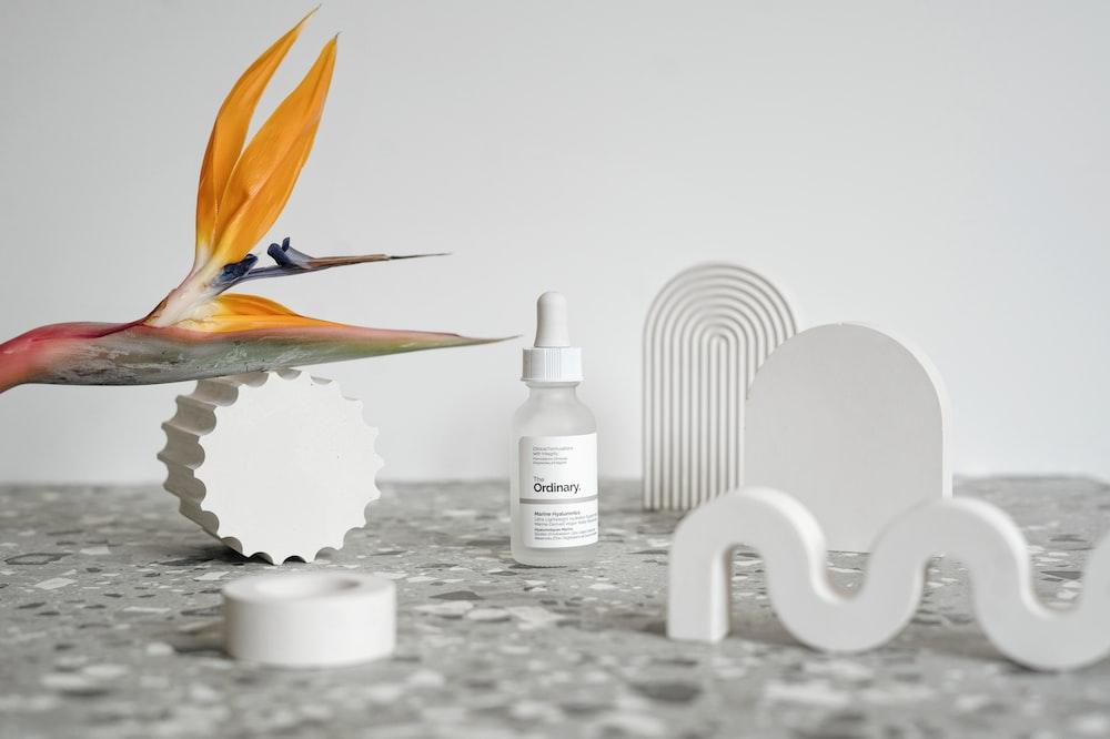 white plastic bottle beside white ceramic swan figurine