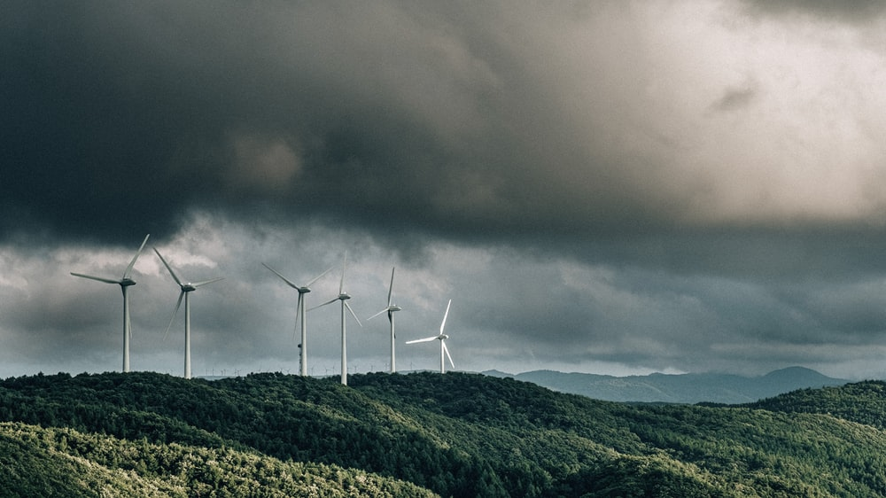 wind turbines on green mountain under gray cloudy sky