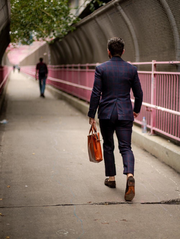 man in black suit jacket and brown pants walking on sidewalk carrying brown leather tote bag