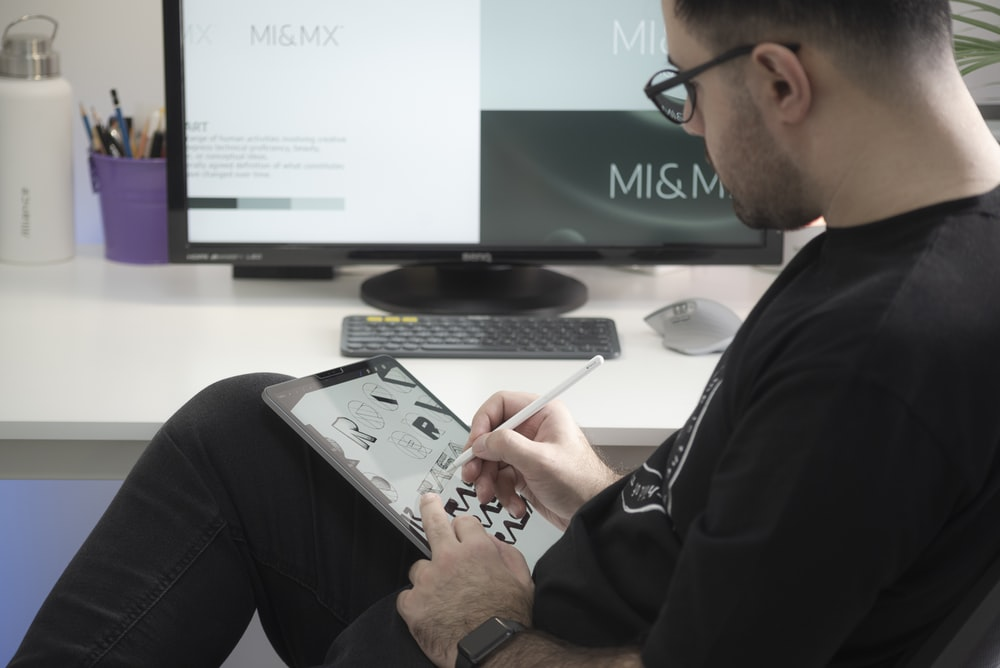 man in black long sleeve shirt sitting beside black flat screen computer monitor