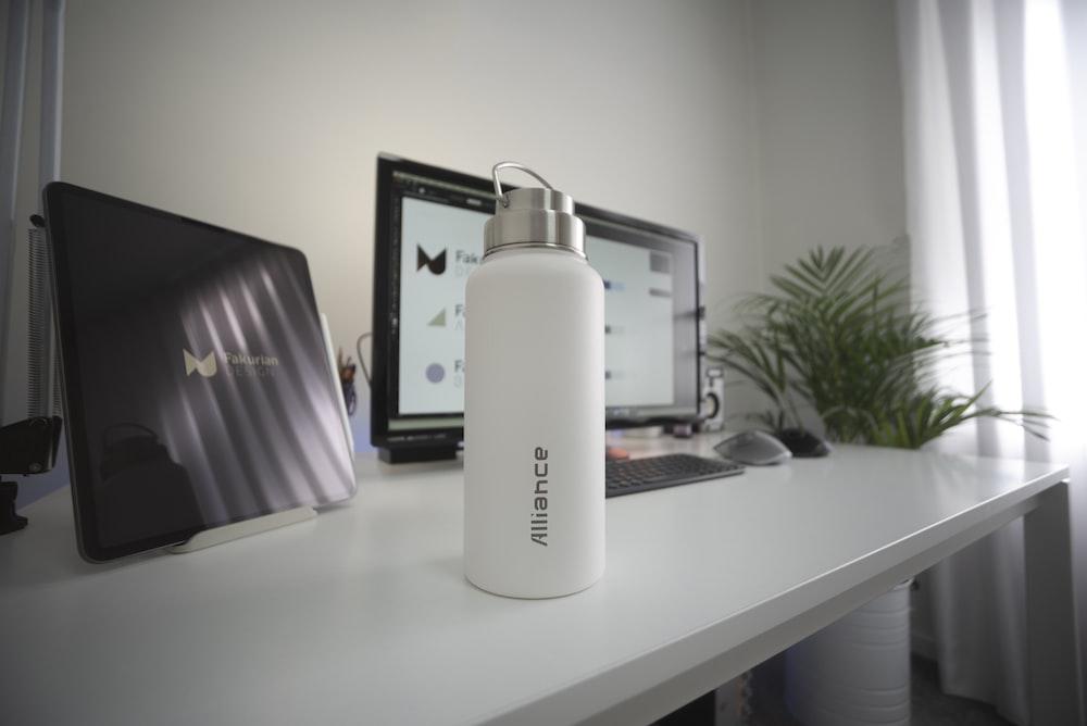 white and black plastic bottle on white table