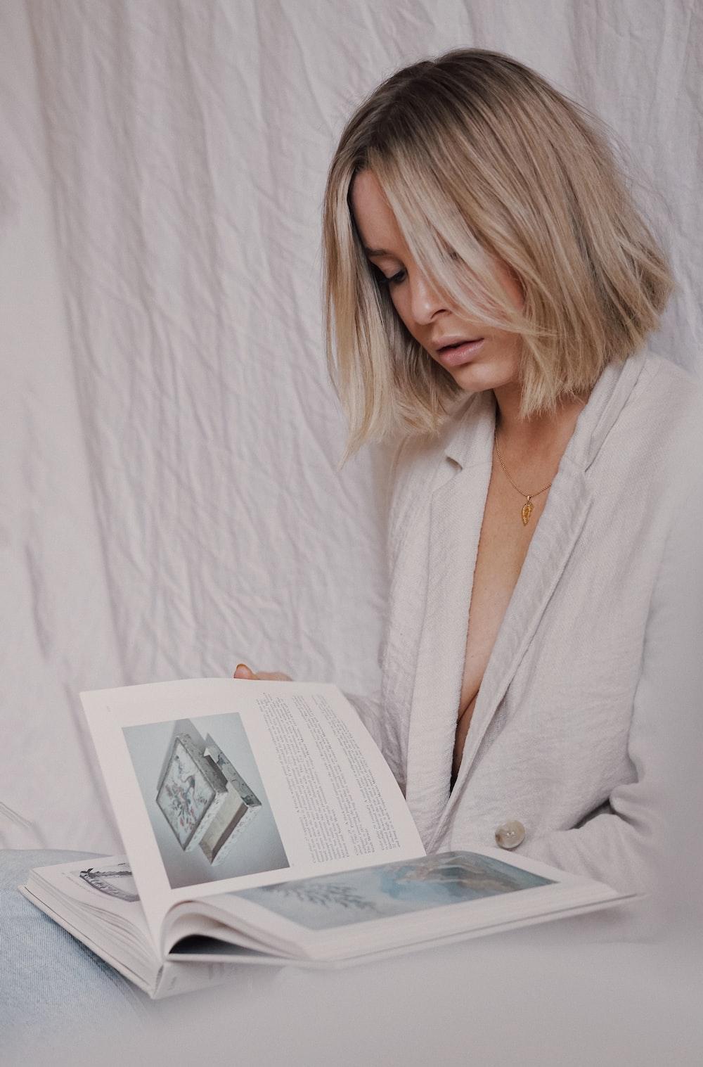 woman in white blazer reading book