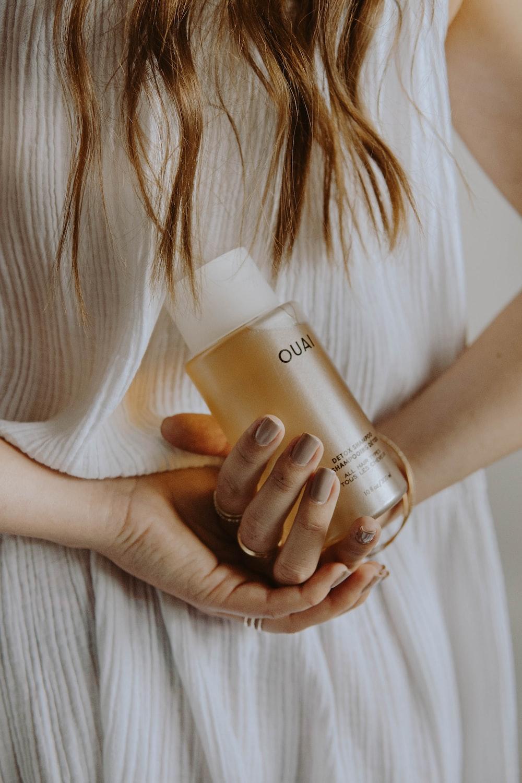 woman in white shirt holding white plastic bottle