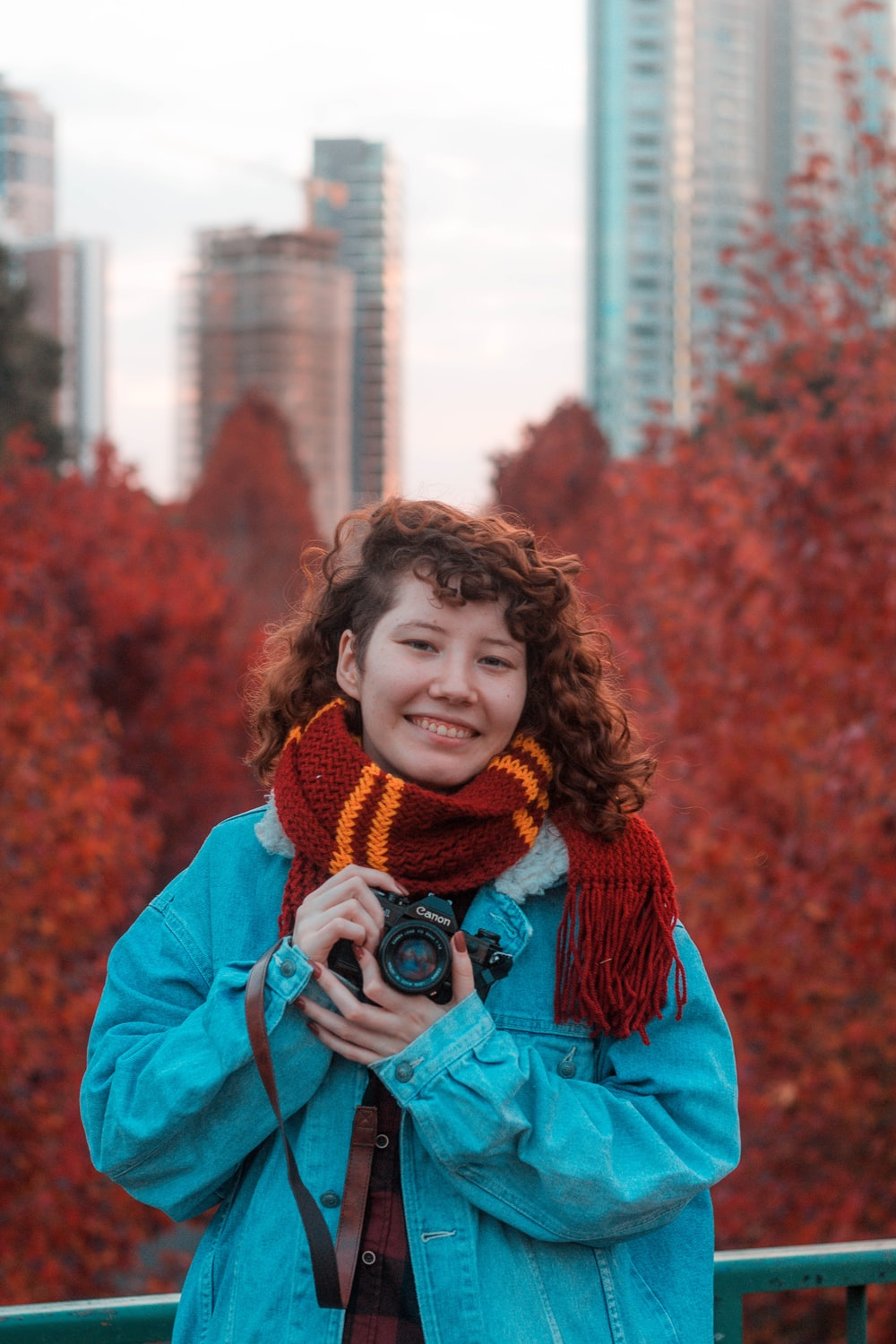 woman in blue jacket holding black camera