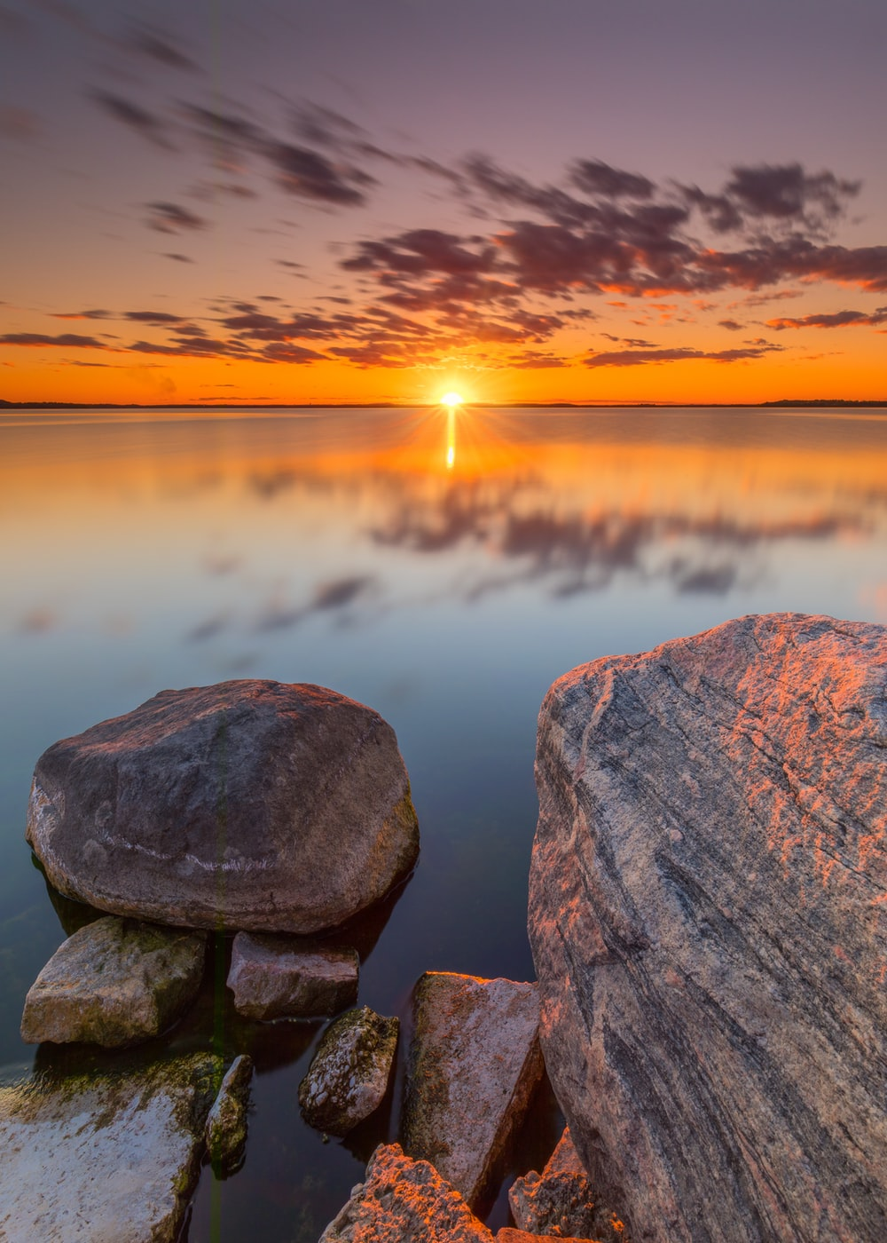 gray and brown rock formation near body of water during sunset