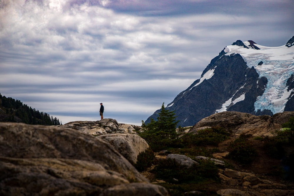 person standing on rock near mountain under cloudy sky during daytime