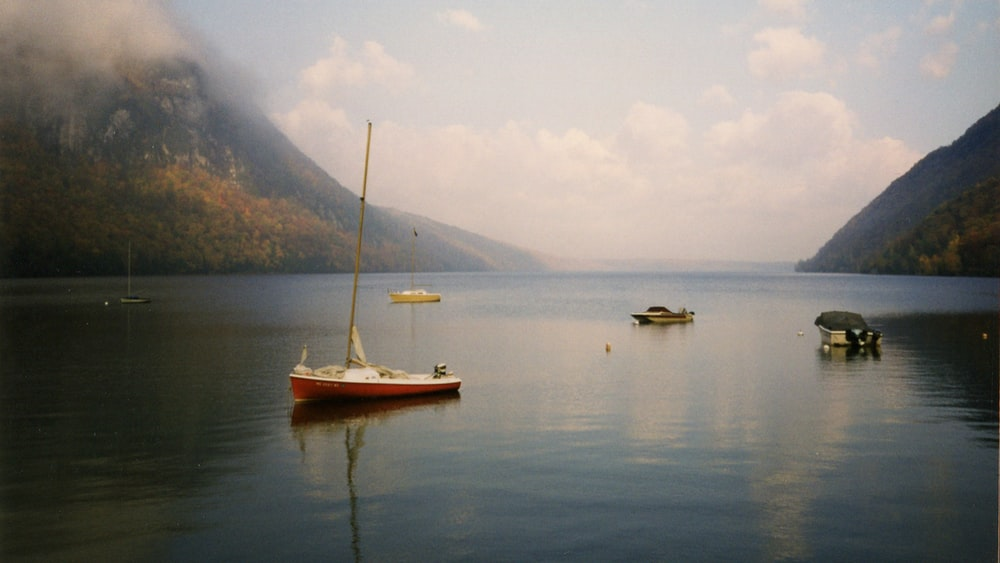 white and brown boat on water near mountain during daytime
