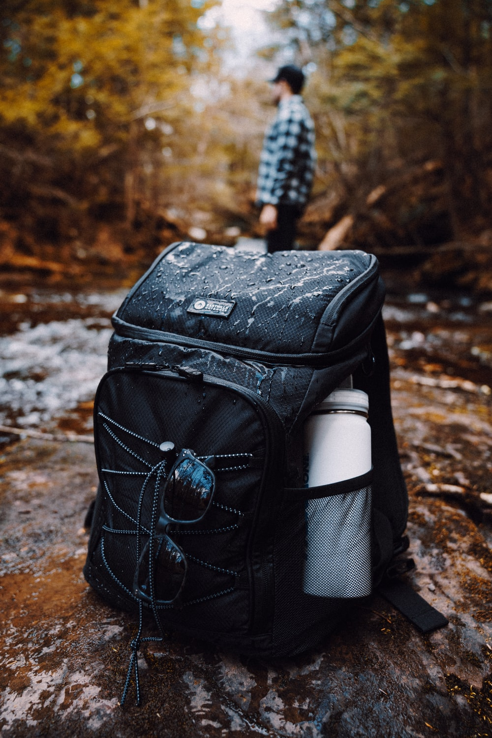 black backpack on brown and white rock