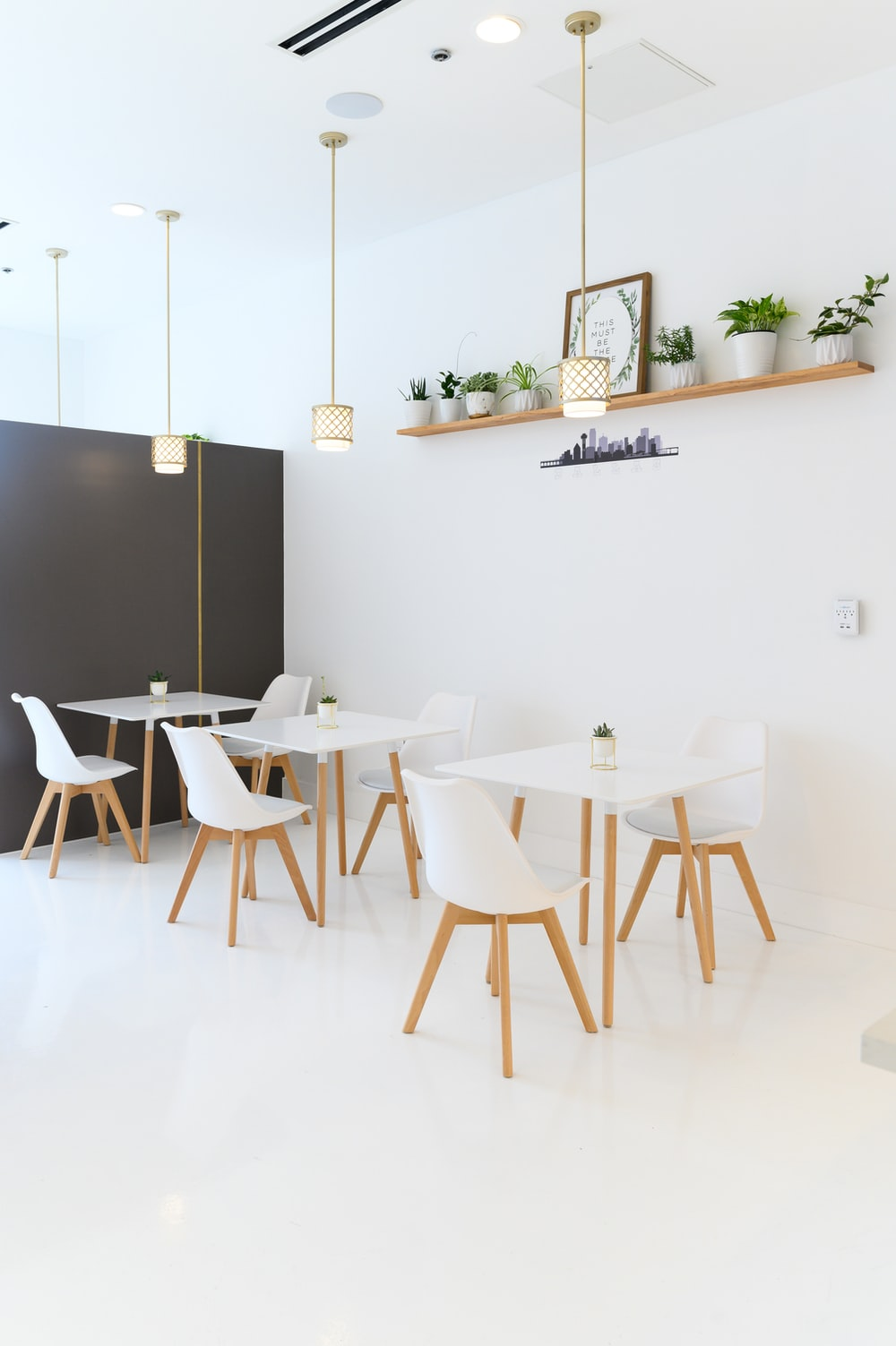 white table and chairs near black wall