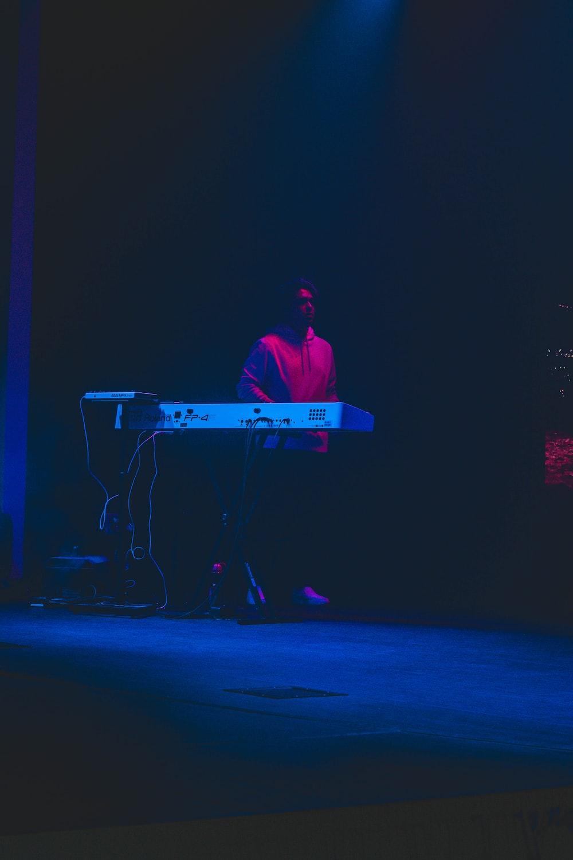 man in red dress shirt playing electric guitar