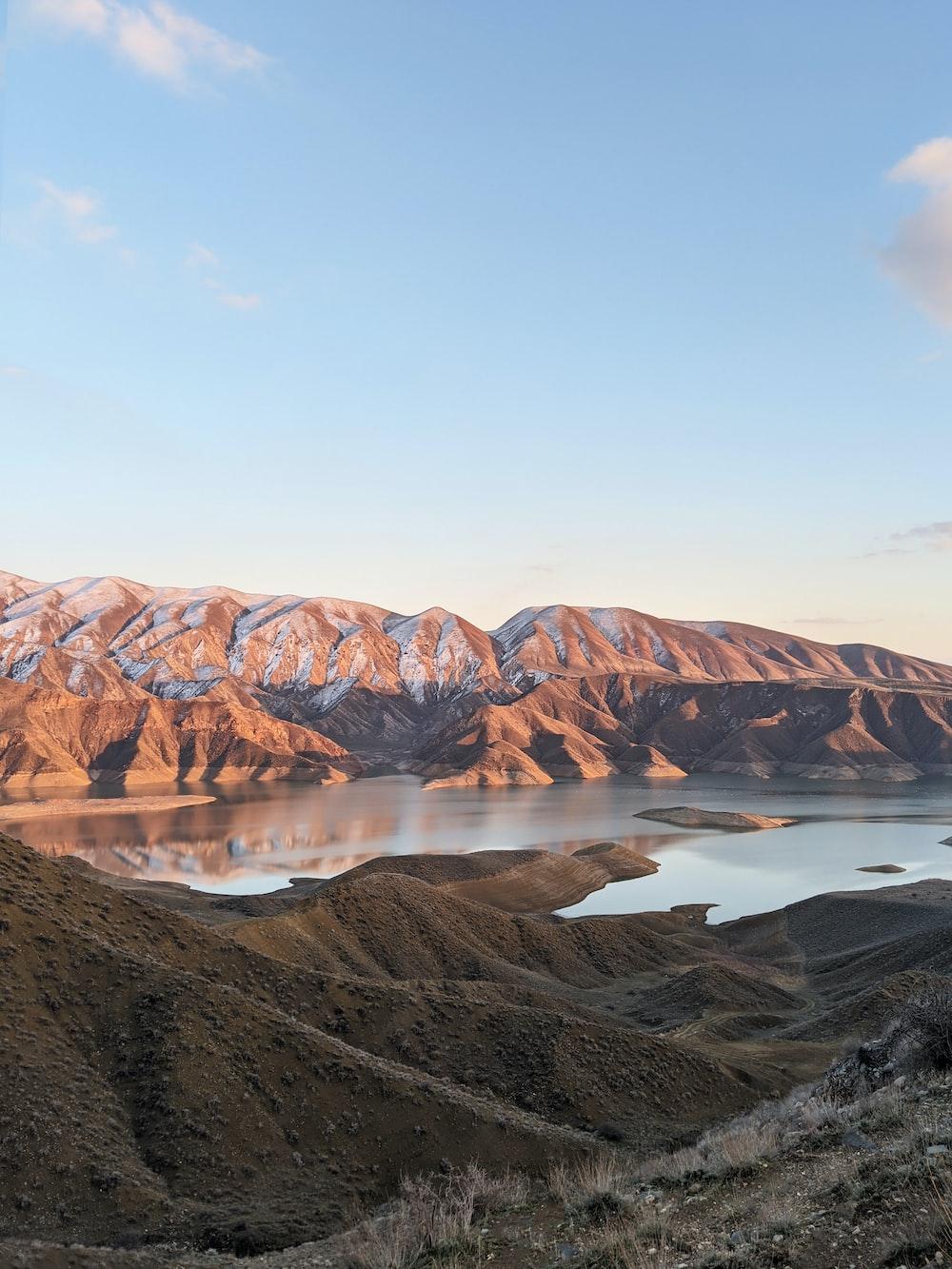 brown mountain near lake under blue sky during daytime