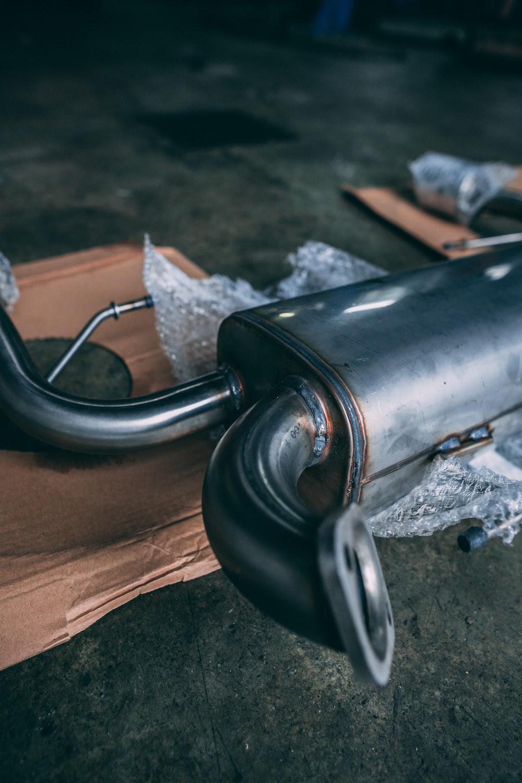 black metal pipe on brown wooden table