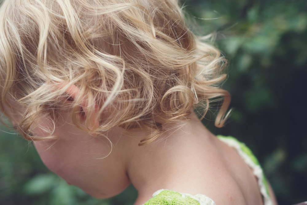 woman with blonde hair holding green leaf