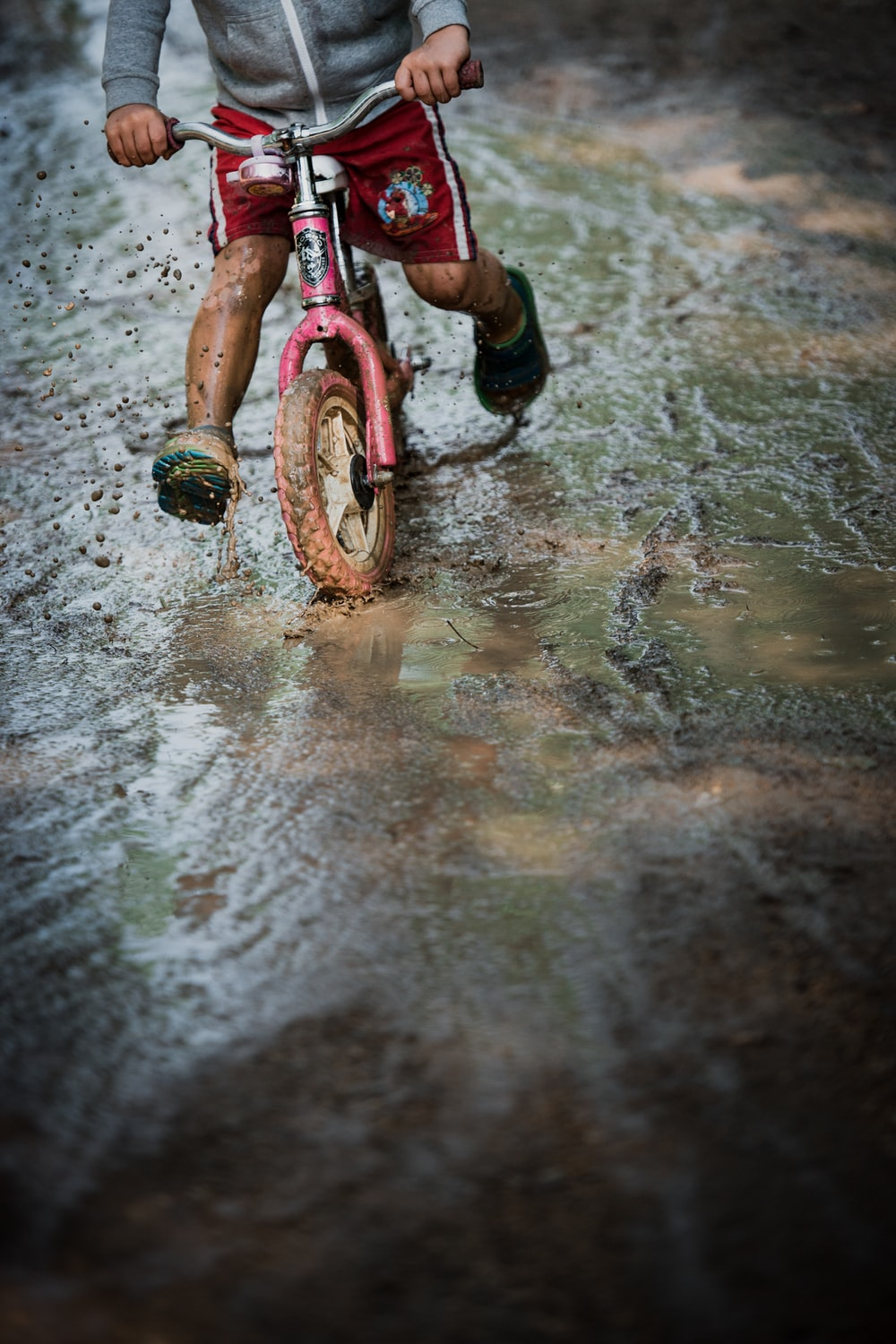 girl in pink and black bicycle on wet ground