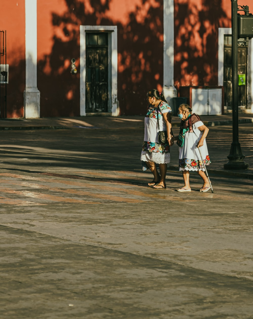 man in white shirt and brown shorts walking on sidewalk during daytime