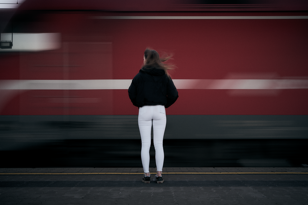woman in black long sleeve shirt and white pants standing on sidewalk