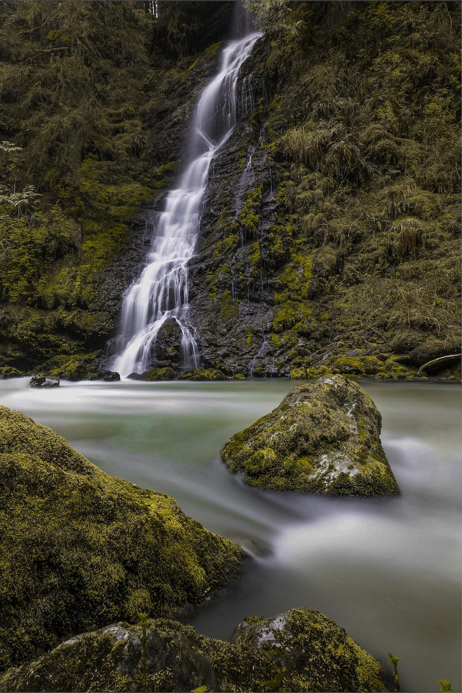 green moss on brown rock near waterfalls