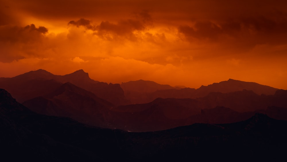 silhouette of mountains under cloudy sky during daytime