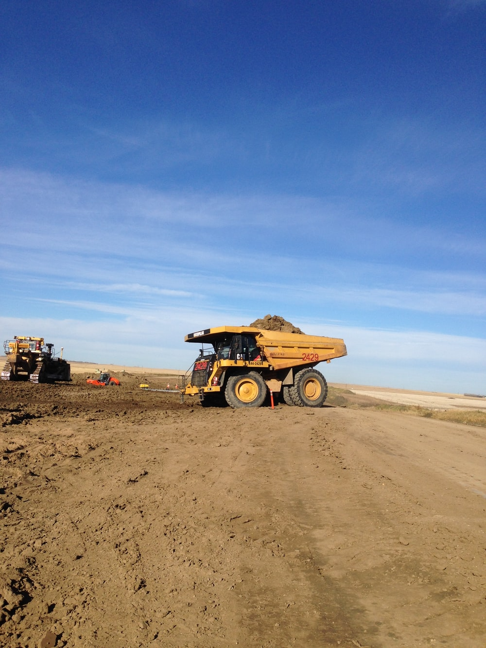 brown utility truck on brown sand under blue sky during daytime