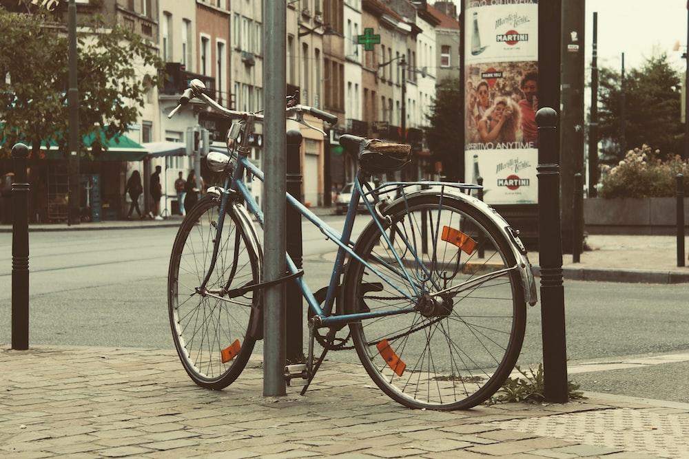 blue city bike parked beside black metal fence during daytime