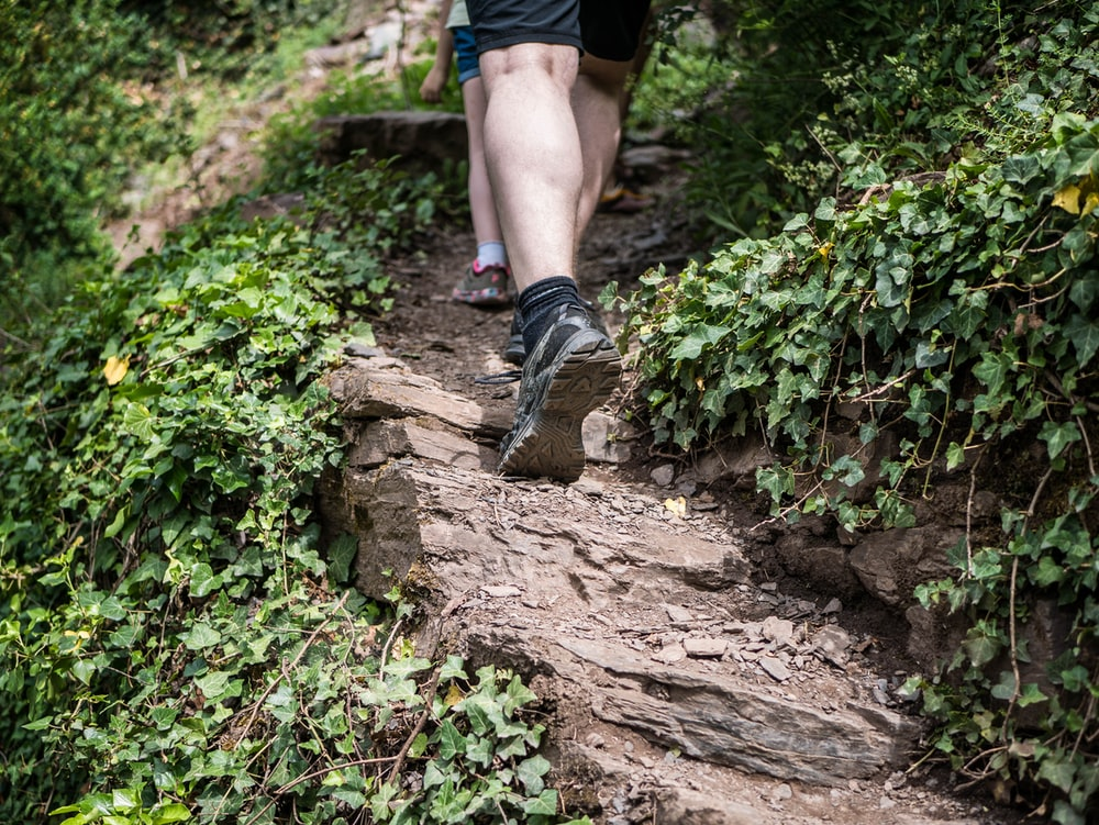person in black hiking shoes standing on brown rock