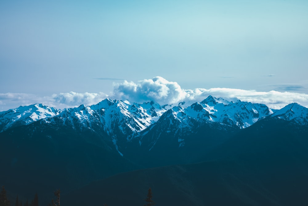 snow covered mountains under cloudy sky during daytime