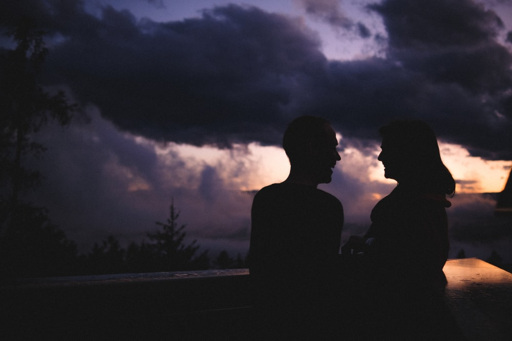 silhouette of 2 person standing on road during night time