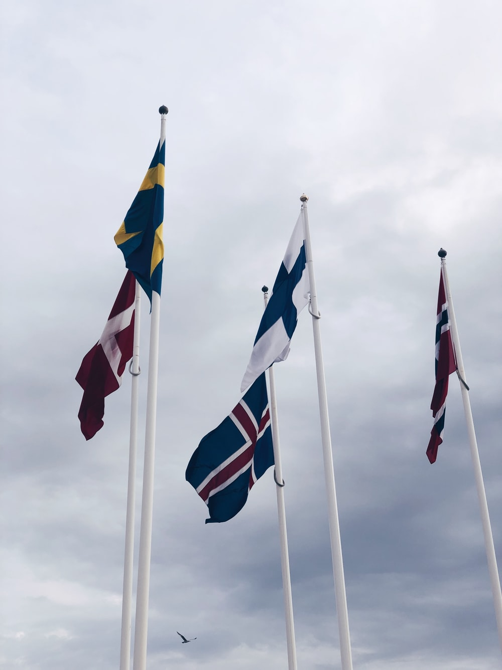 three flags on white pole during daytime