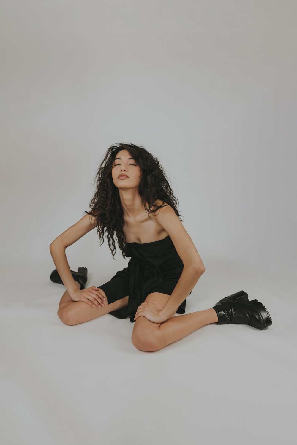 woman in black spaghetti strap dress sitting on white floor