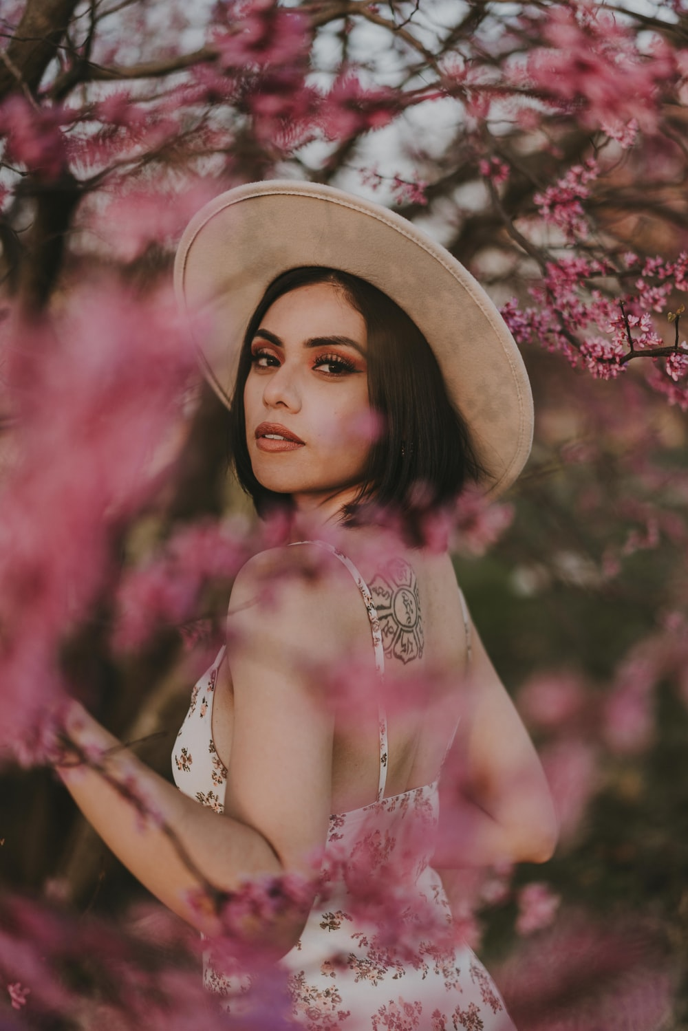 woman in pink floral dress wearing brown hat