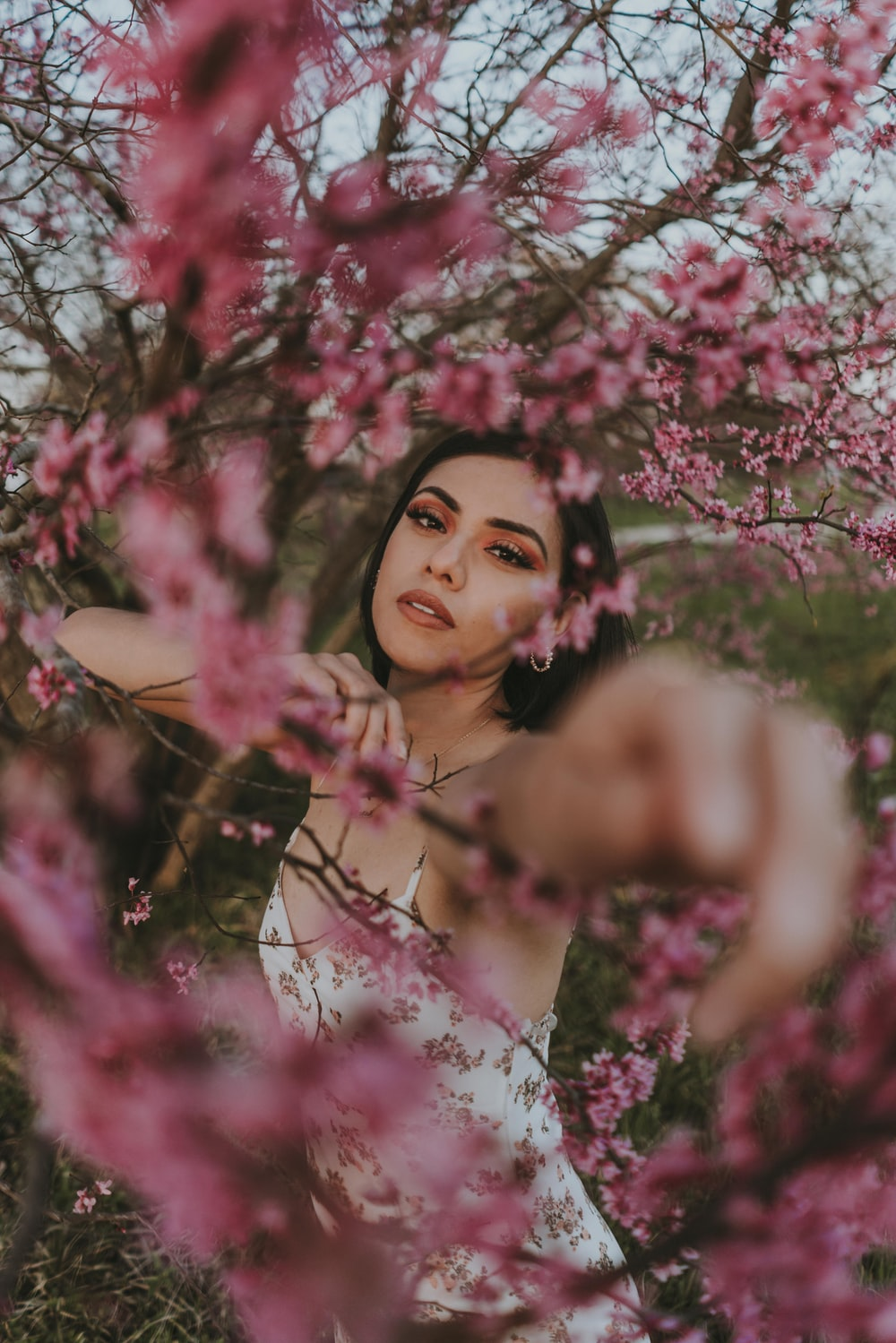 woman in pink floral dress standing under pink cherry blossom tree during daytime