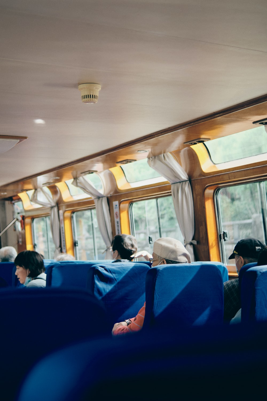 people sitting on blue bus seat