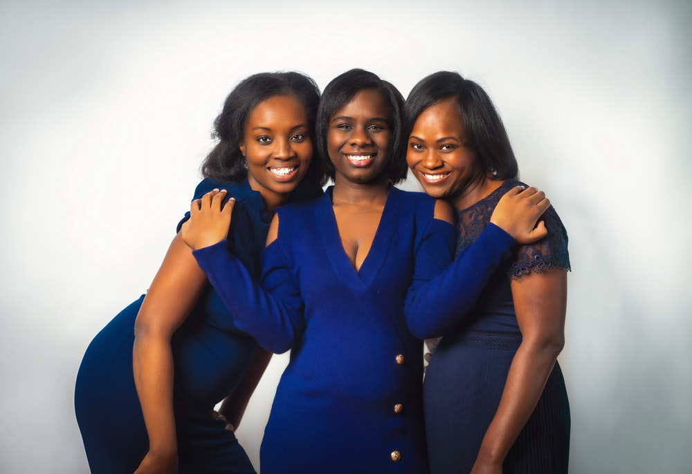 3 women in blue button up shirts smiling