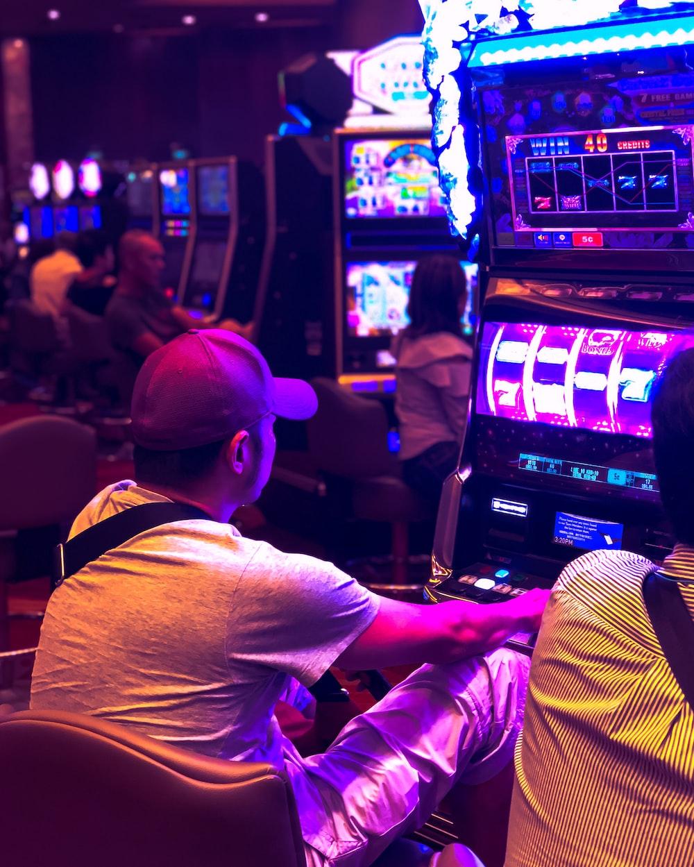 man in white t-shirt playing arcade game