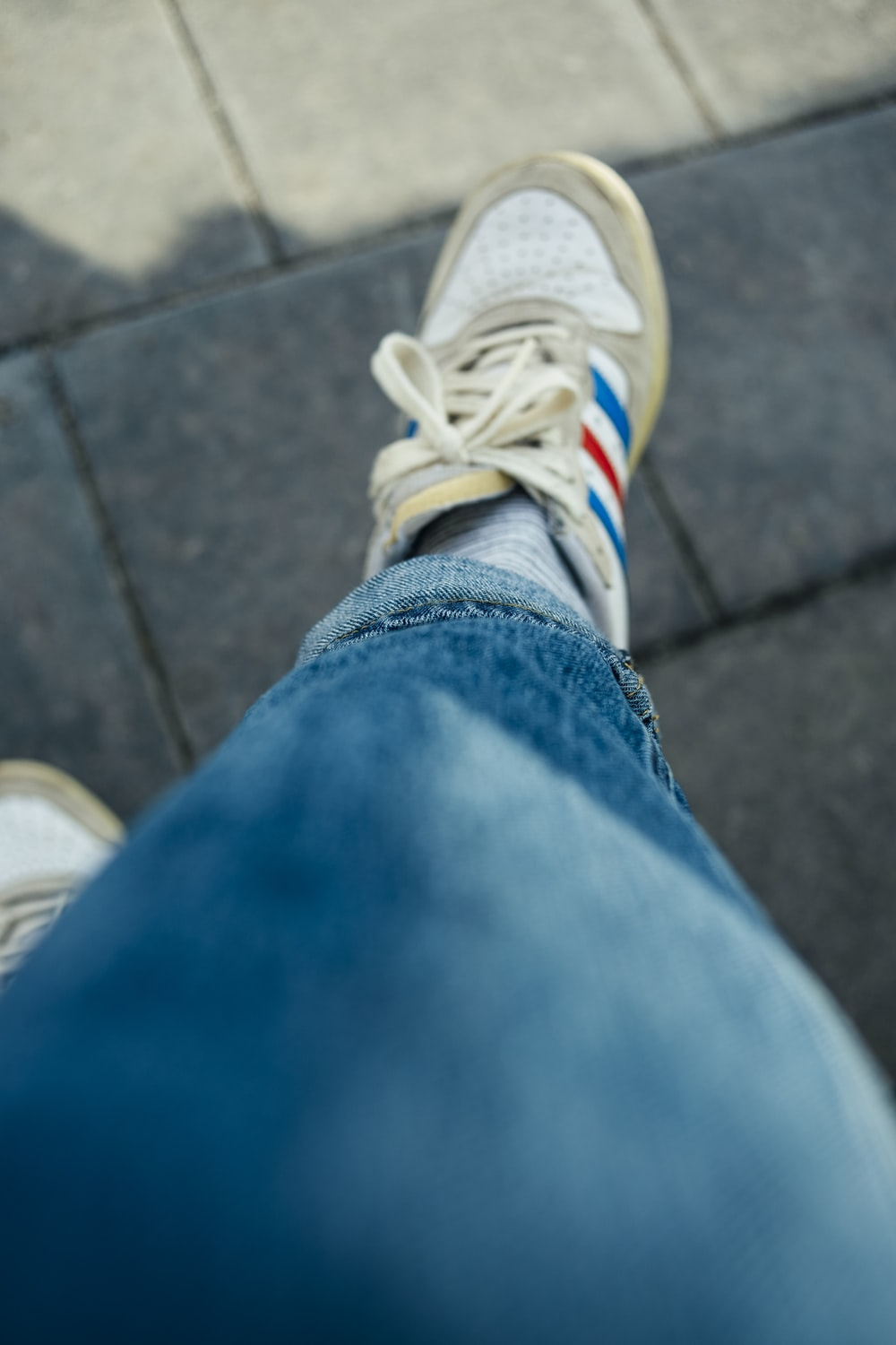 person in blue denim jeans wearing white and yellow adidas sneakers
