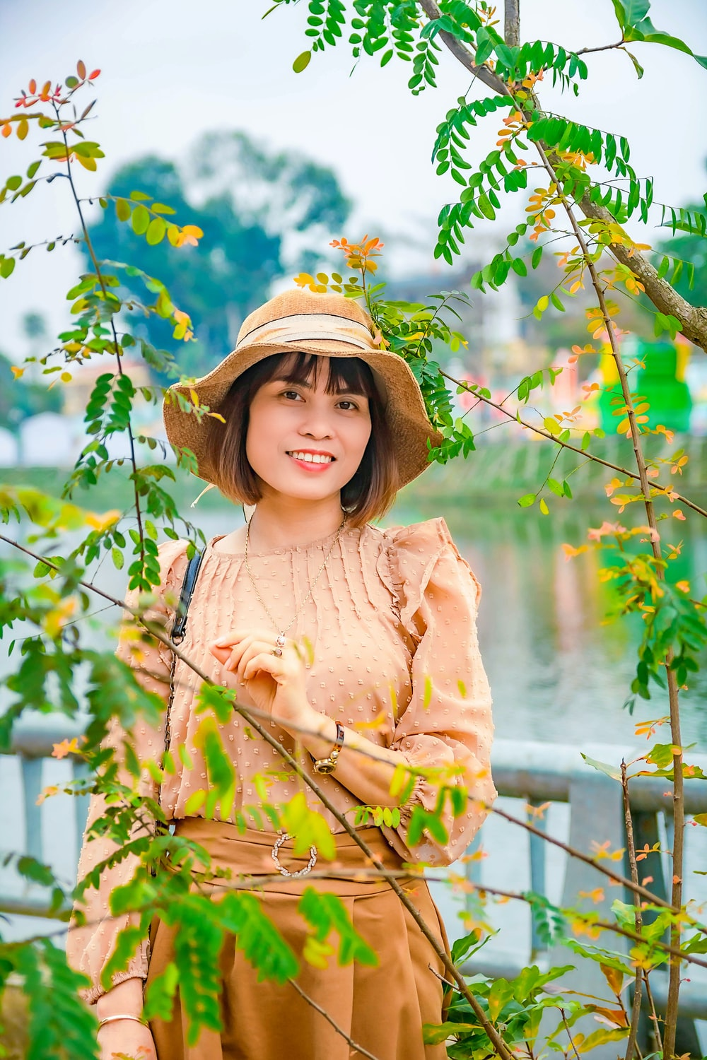 girl in brown long sleeve shirt and brown hat standing near green plants during daytime