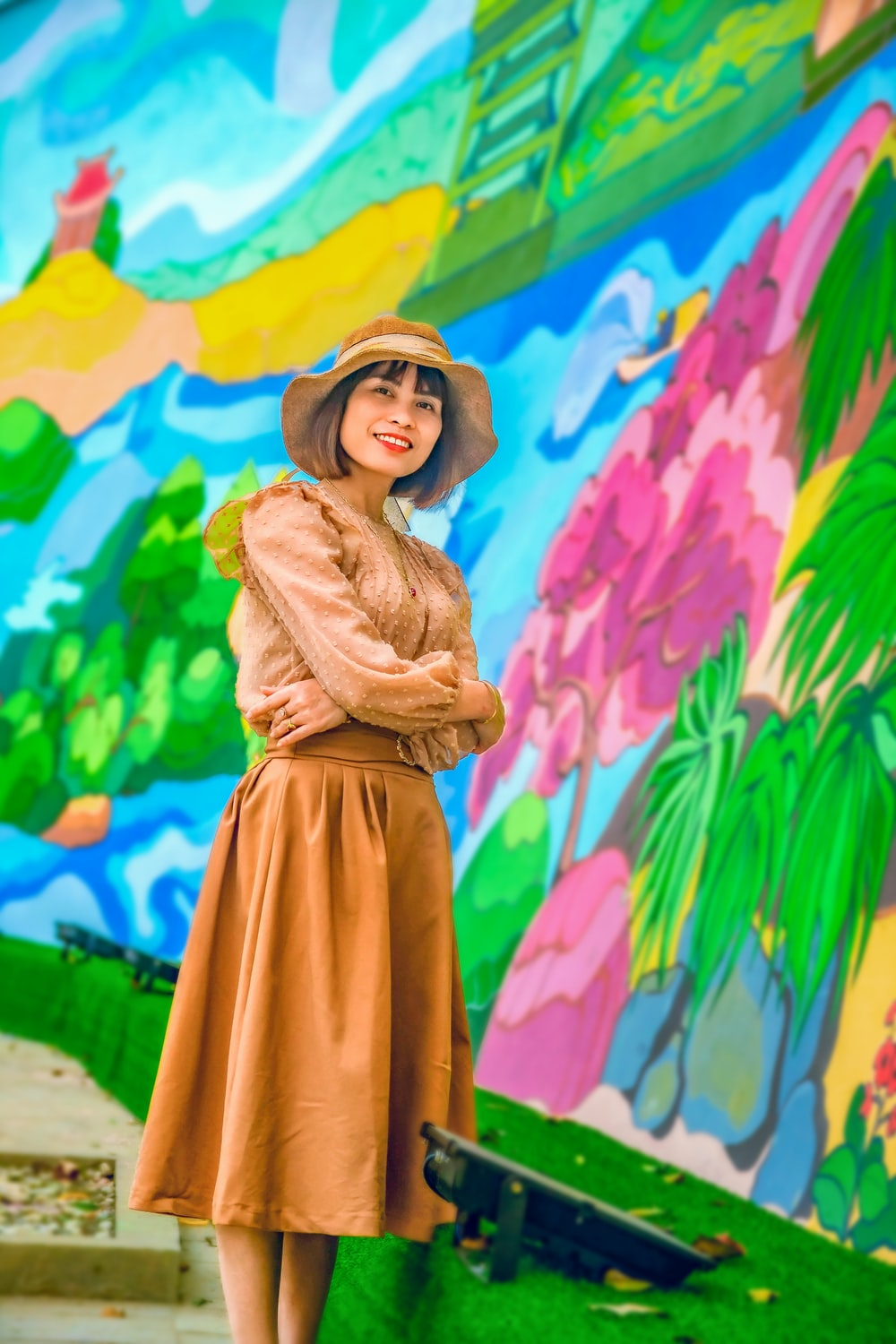woman in brown coat standing near wall with graffiti