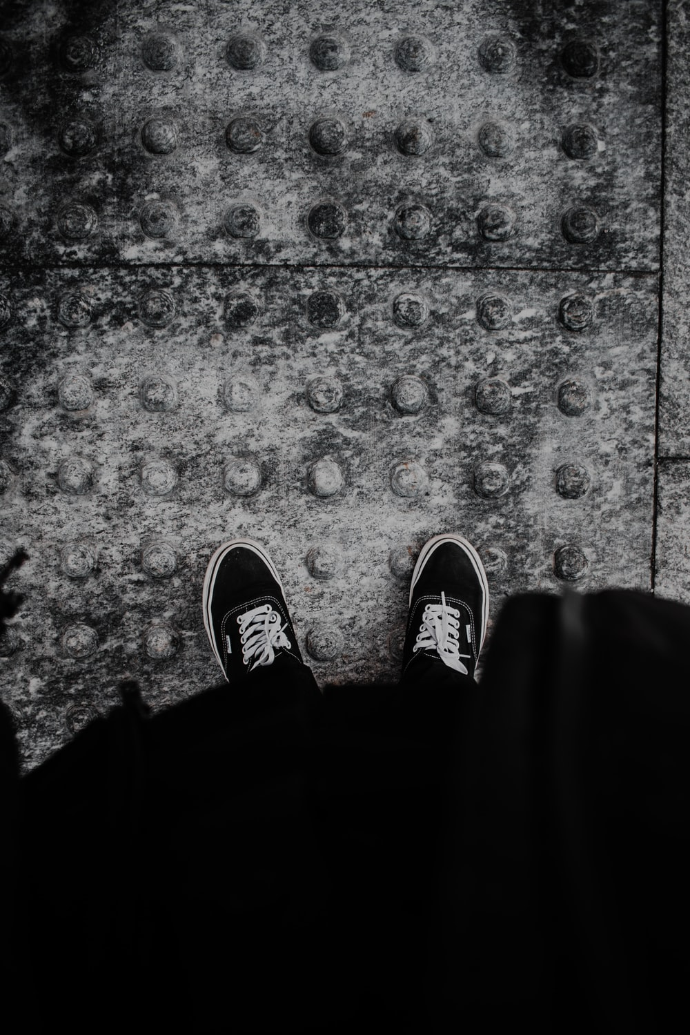 person in black pants and black and white sneakers