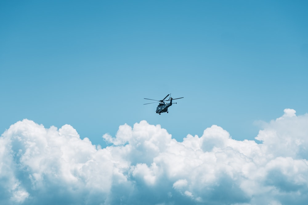 black helicopter flying in the sky during daytime
