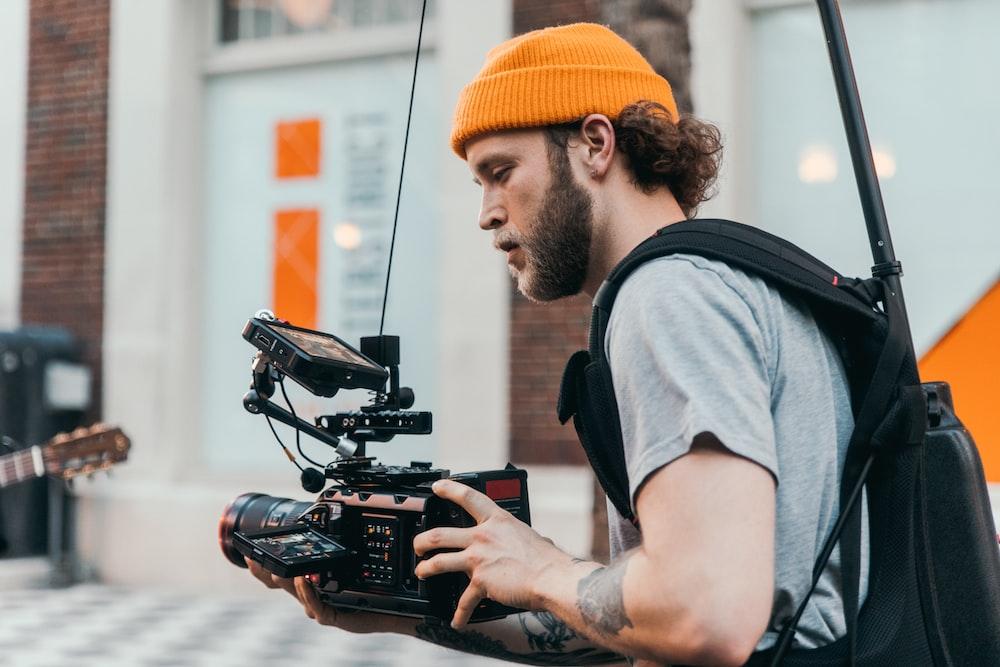 man in gray crew neck t-shirt using black video camera