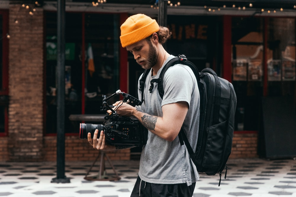 man in gray crew neck t-shirt and yellow knit cap holding black dslr camera