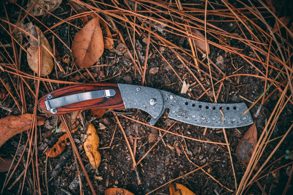 black and brown folding knife on brown dried leaves