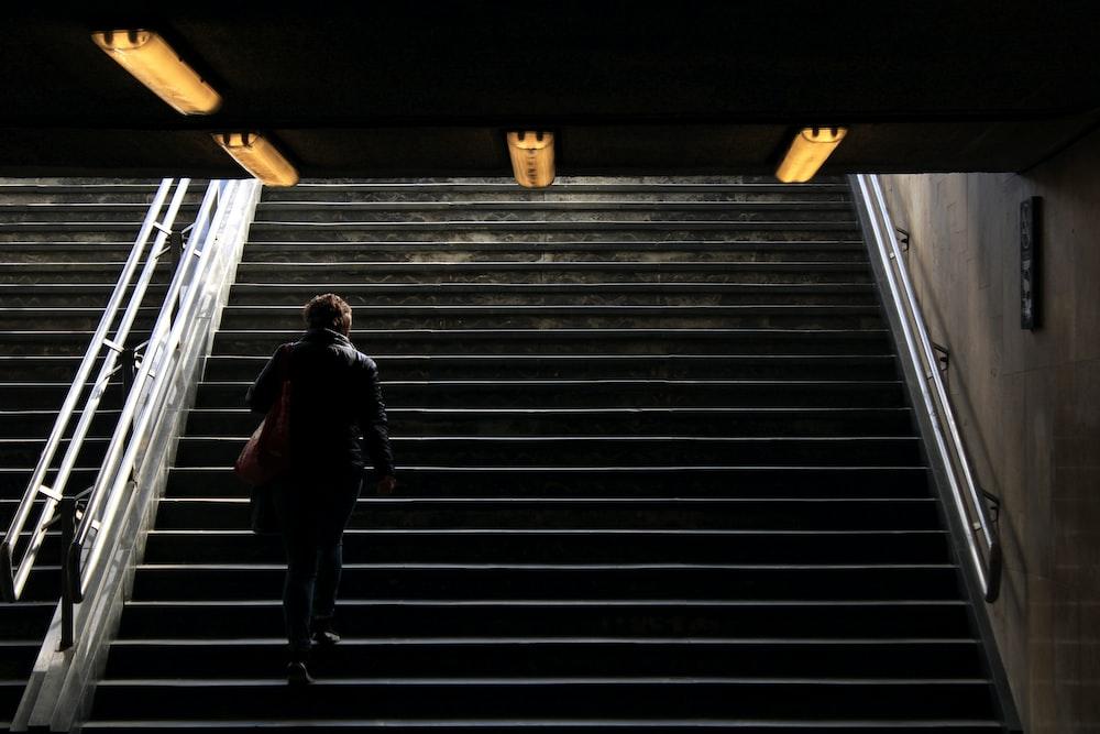 man in black jacket walking on stairs