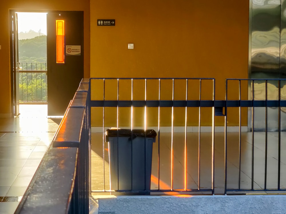 black trash bin beside brown concrete wall